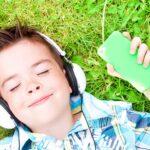 Child listening to audio in grass
